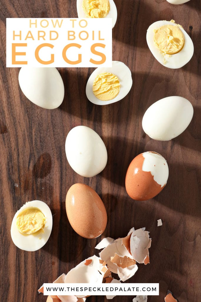 Hard boiled eggs are peeled on a dark wood cutting board with the text 'how to hard boil eggs'