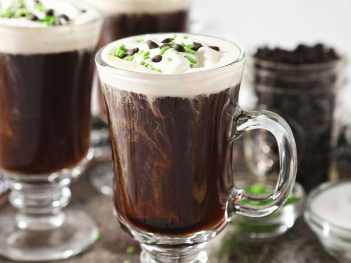 Three Irish Coffees sit on a silver tray, garnished with whipped cream, chocolate and green sprinkles