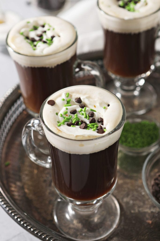 Three Irish Coffee drinks with whipped cream, chocolate and green sprinkles on a silver tray