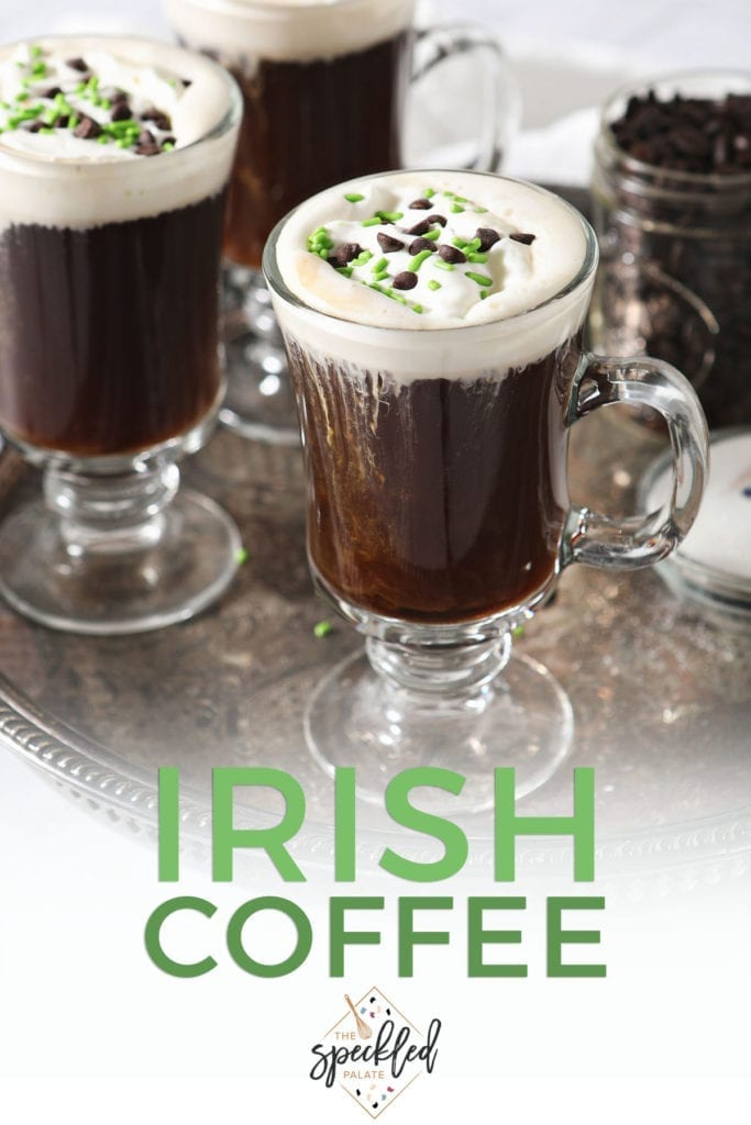 Three coffee cocktails with whipped cream, chocolate and green sprinkles on a silver tray with the text 'Irish coffee'