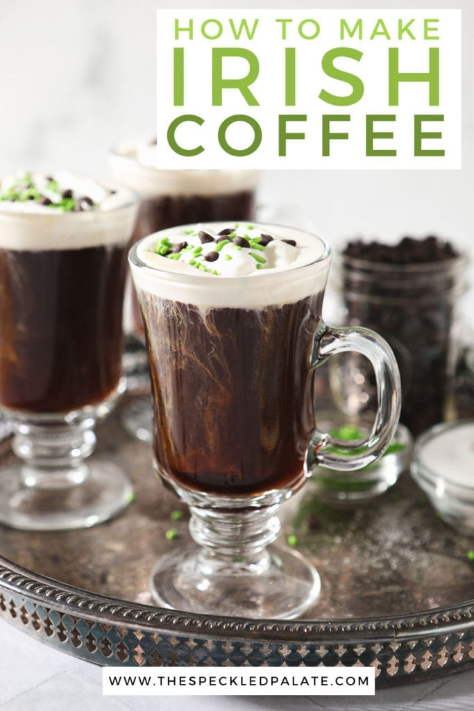 Three Irish Coffees sit on a silver tray, garnished with whipped cream, chocolate and green sprinkles with the text 'How to make Irish Coffee'