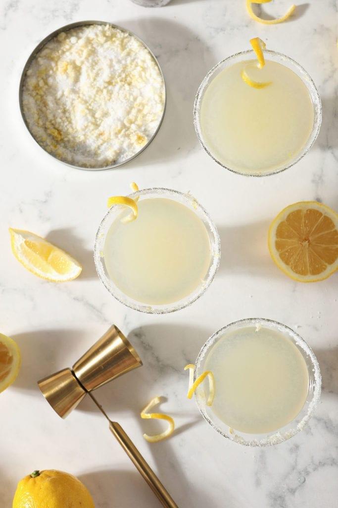 Three Lemon Drops sit on a marble surface next to lemon sugar, lemon wedges and a golden jigger