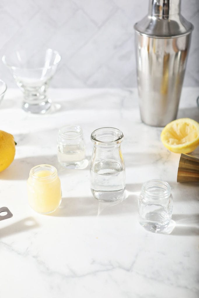 Lemon juice, simple syrup, vodka and Cointreau in bottles on a marble surface surrounded by other mixed drink materials