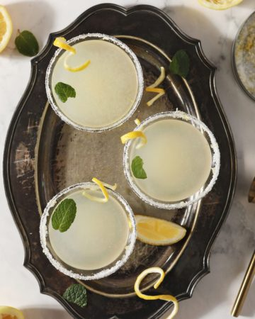 Three Lemon Drop Martinis garnished with mint leaves and lemon twists sit on a silver tray