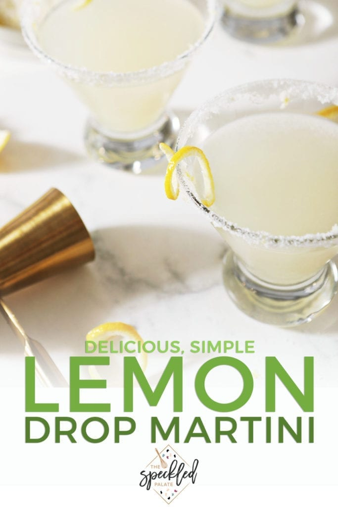 Two martini glasses rimmed with sugar and garnished with a lemon twist on marble with the text 'delicious, simple lemon drop martini'