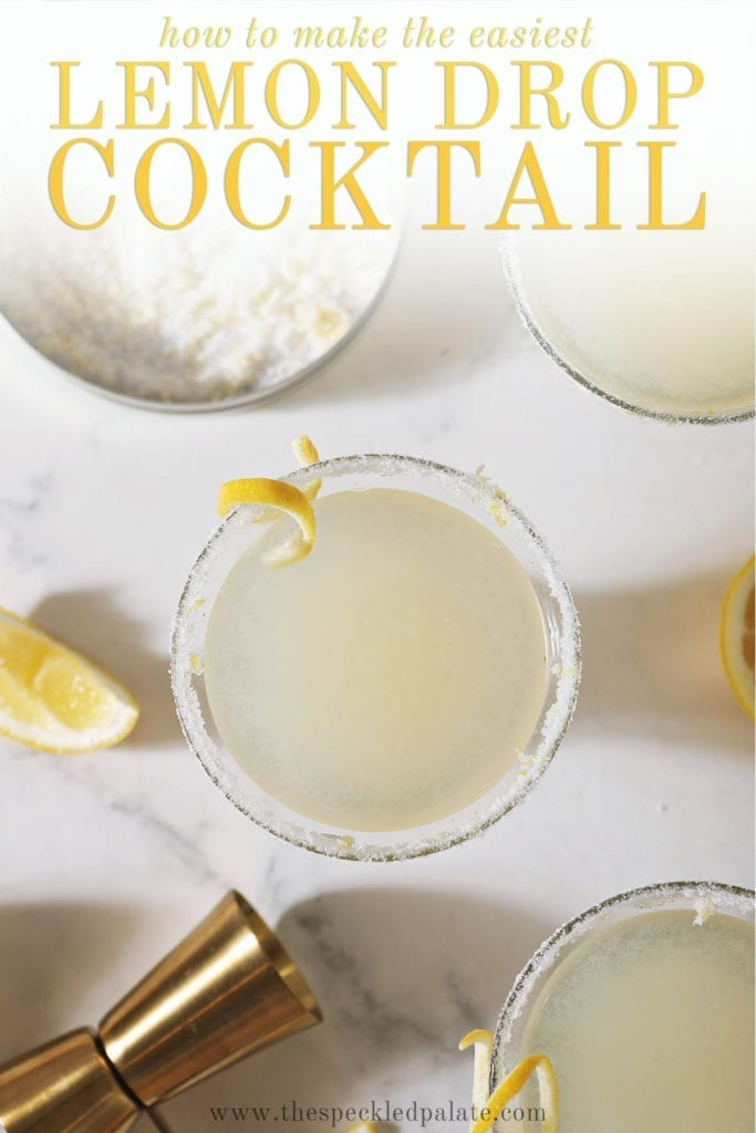 Three Lemon Drops sit on a marble surface next to lemon sugar, lemon wedges and a golden jigger with the text 'how to make the easiest lemon drop cocktail'