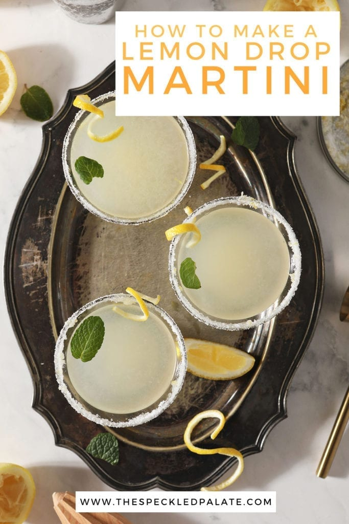 Three Lemon Drop Martinis garnished with mint leaves and lemon twists sit on a silver tray with the text 'how to make a lemon drop martini'