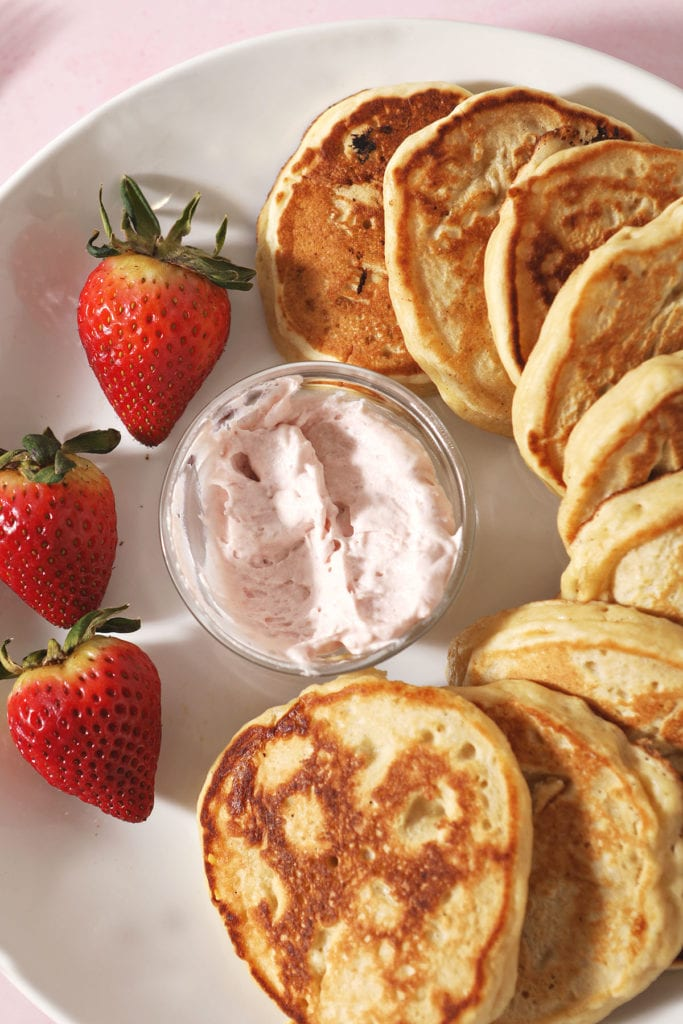 A plate of pancakes circles around a bowl of strawberry whipped cream with fresh strawberries