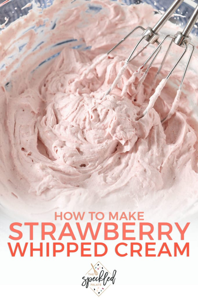 Whisks in a bowl of homemade whipped cream with the text 'how to make strawberry whipped cream'