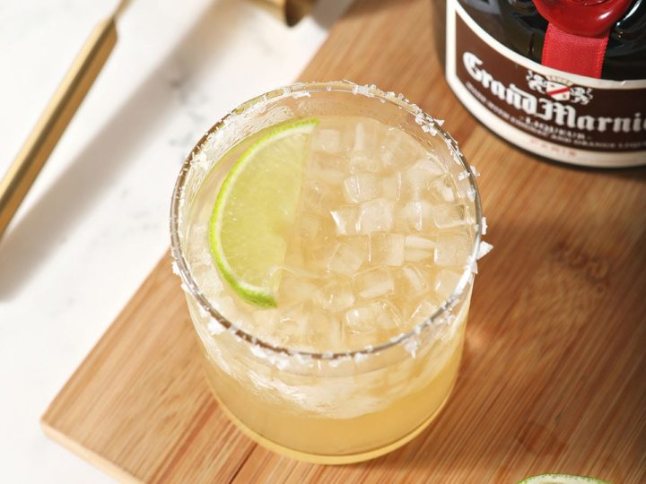 A margarita garnished with a lime sits next to a bottle of Grand Marnier