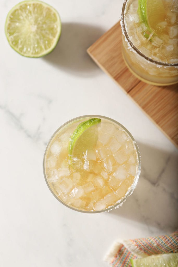 A top shelf margarita garnished with a lime on marble