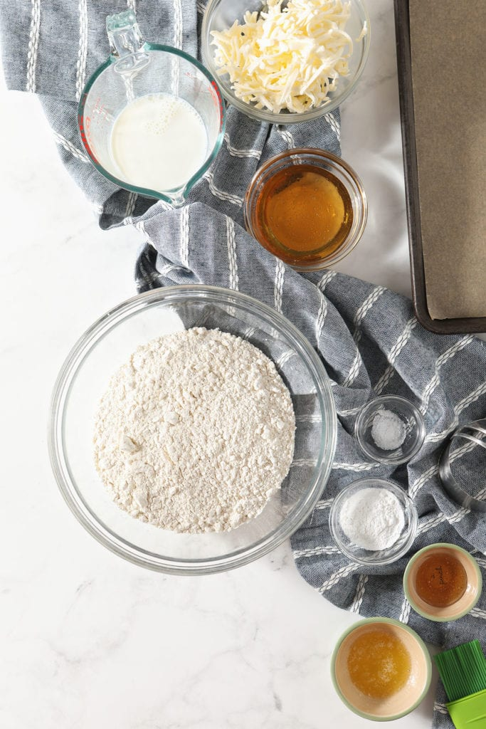Homemade biscuit ingredients in bowls on marble