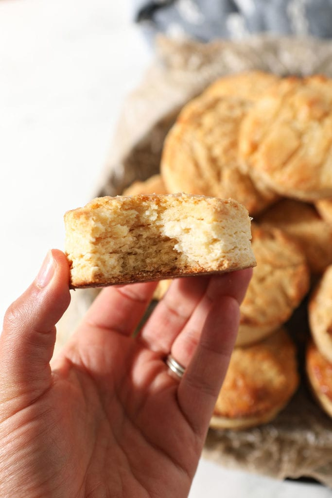 A hand holds a bitten-into honey butter biscuit