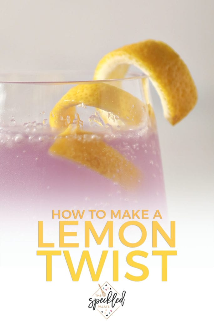 A cocktail twist sits on top of a purple drink with the text 'how to make a lemon twist'
