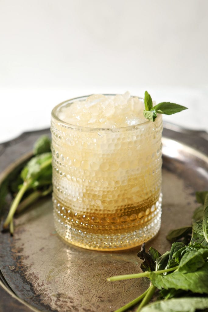 A mint julep on a silver tray with a mint garnish