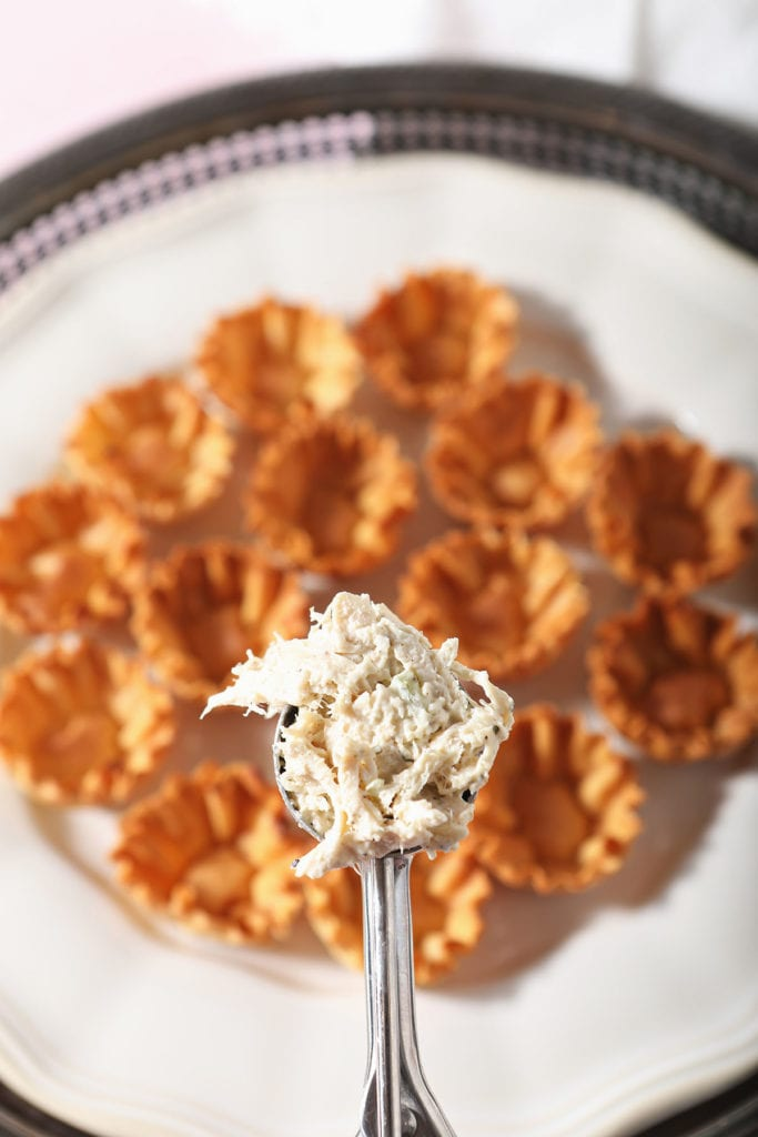 A scoop of chicken salad over a plate of phyllo shells