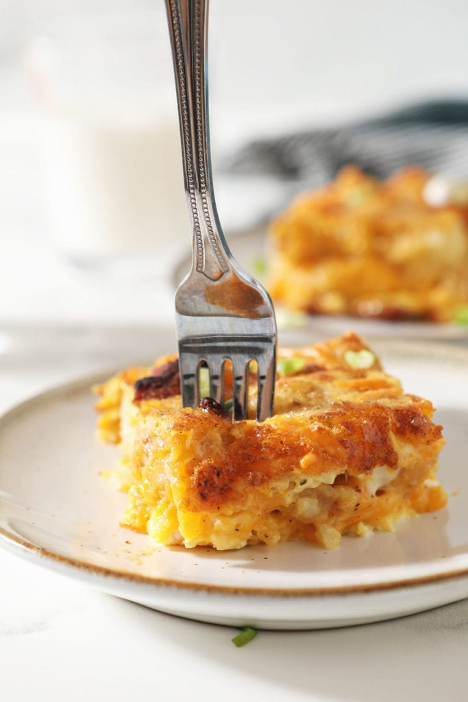 A fork cuts into a slice of breakfast tater tot casserole