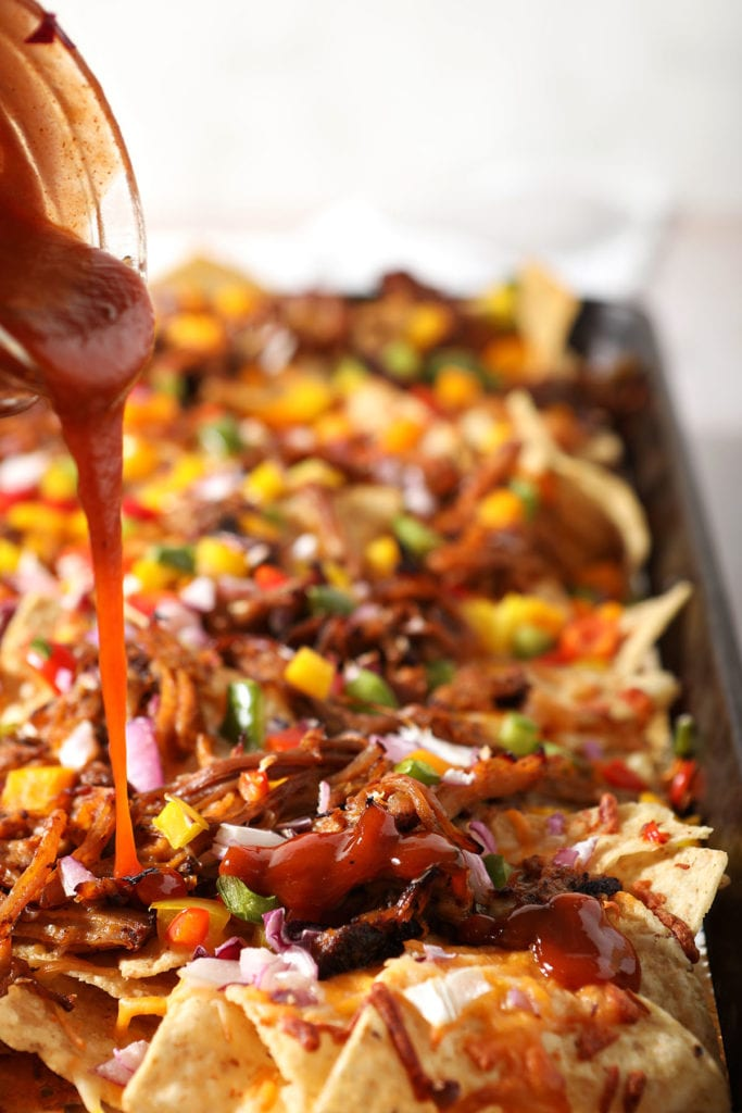 Barbecue sauce drizzles on top of pulled pork nachos