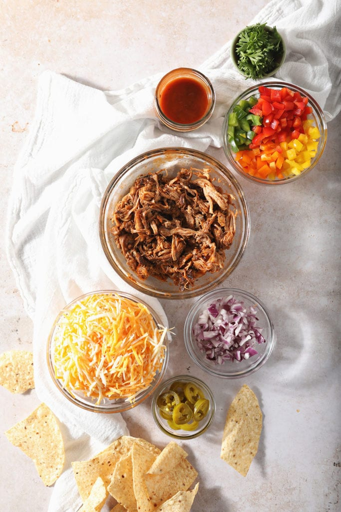 Bowls holding barbecue nacho ingredients in a white kitchen cloth