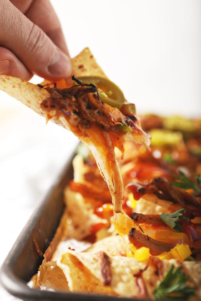 A person lifts a BBQ nacho from a pan