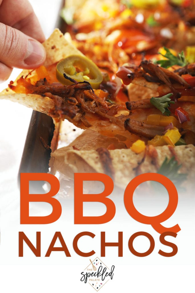 A person lifts a nacho from a tray with the text BBQ nachos