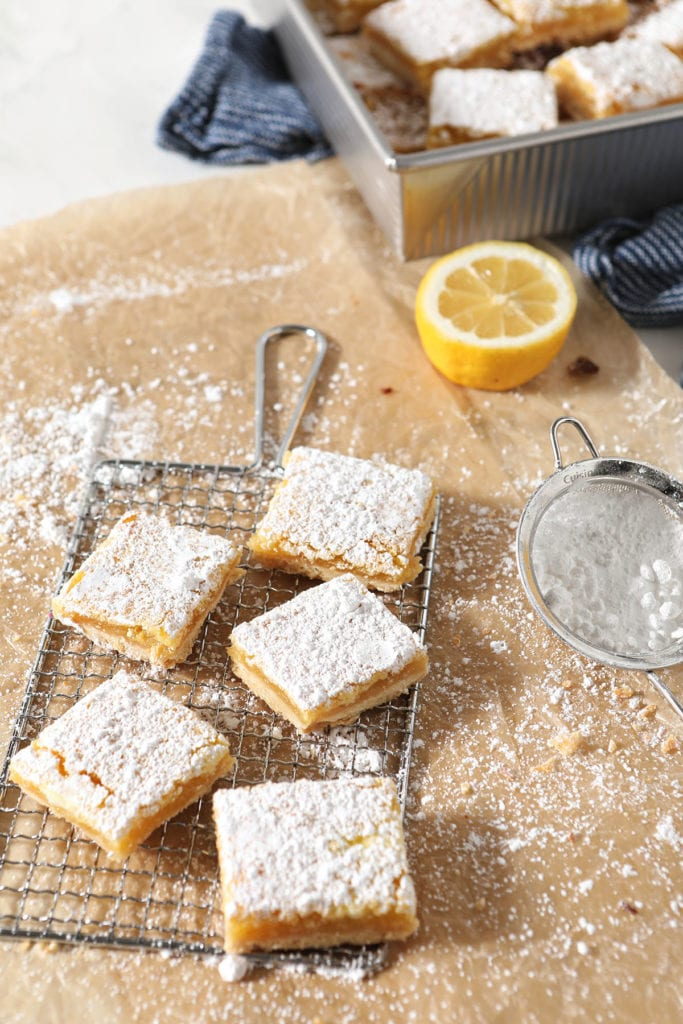 Five lemon bars sit on a metal cooling rack next to a tray of bars