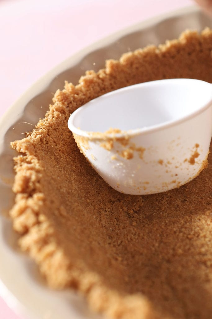 A white measuring scoop pushes graham cracker crumbs into place