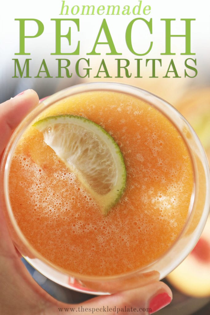 A hand holds a peach margarita garnished with a lime wedge with text homemade peach margaritas