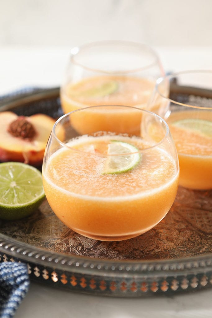 Three orange margaritas on a metal tray with limes
