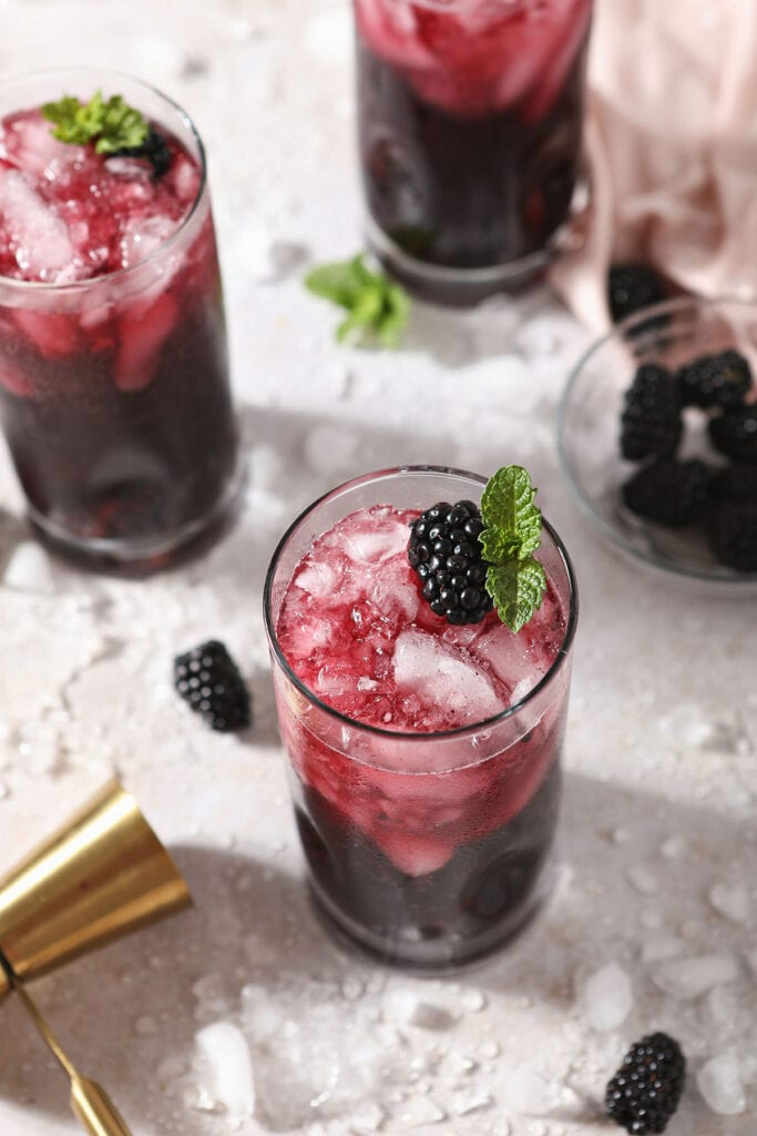 Three red wine spritzers garnished with blackberries and mint
