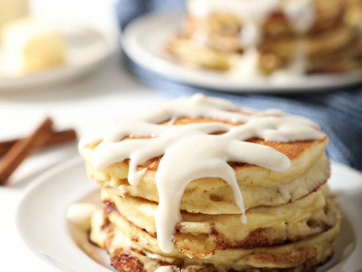 A stack of Cinnamon Roll Pancakes with glaze on a white plate