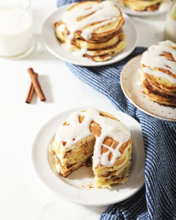 Three plates of pancakes with cream cheese glaze