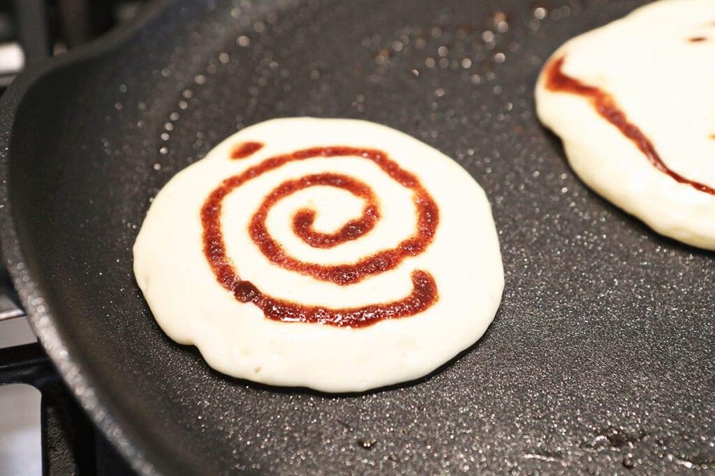 A cinnamon swirl inside a pancake on a skillet