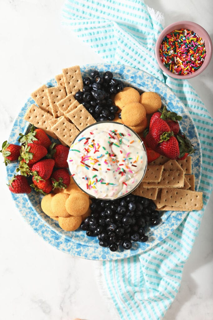 Funfetti Dip in a bowl with on a platter of crackers, cookies and fresh fruit