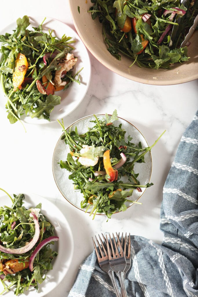 Three white plates hold grilled peach salad next to a salad bowl