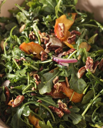 Close up of an arugula salad with peaches