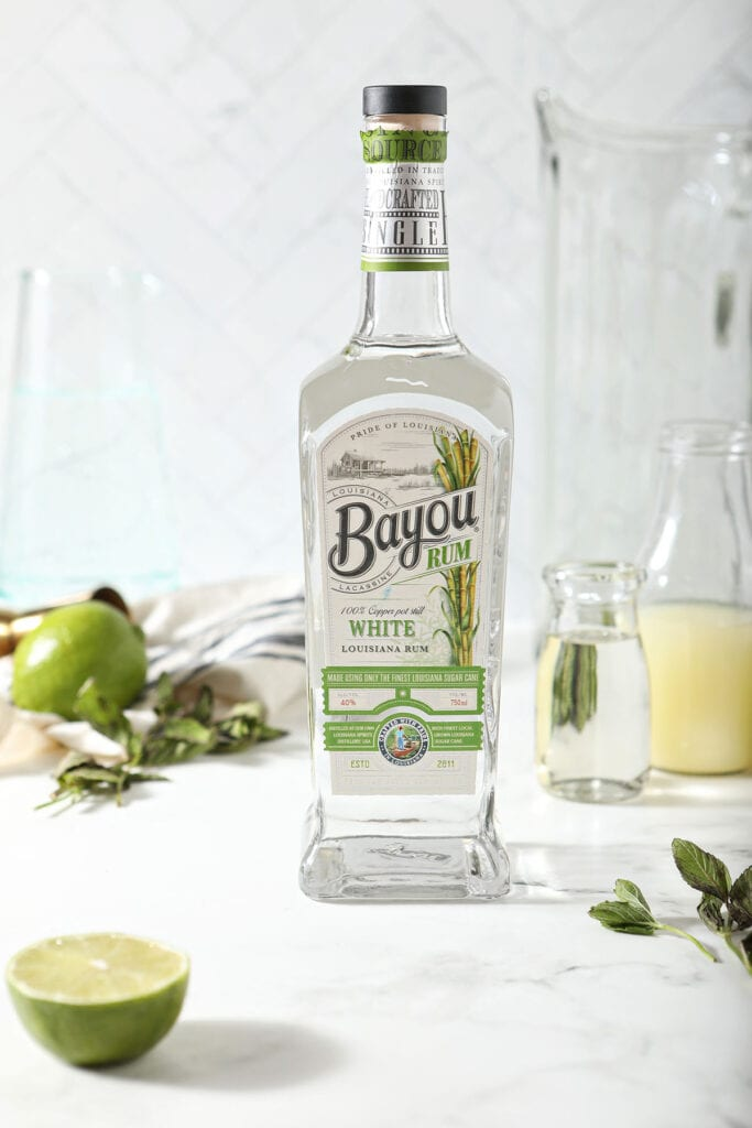 A bottle of Bayou white rum with other ingredients on marble