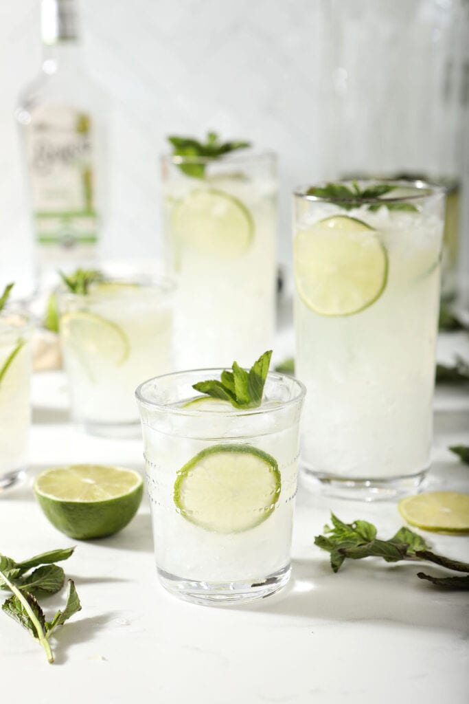 Five mojito glasses with a pitcher and a bottle of rum
