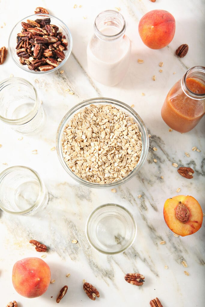 Ingredients to make vegan overnight oats in bowls on marble