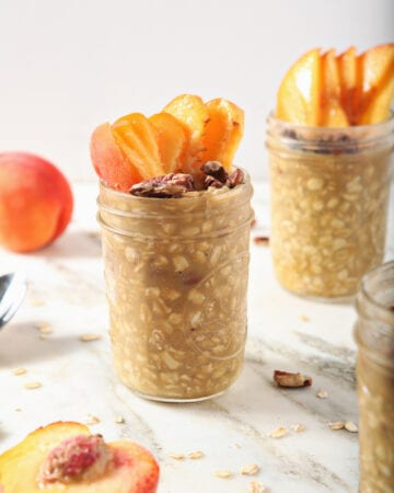 Three jars of Peach Overnight Oats with peach slices and toasted pecan garnishes