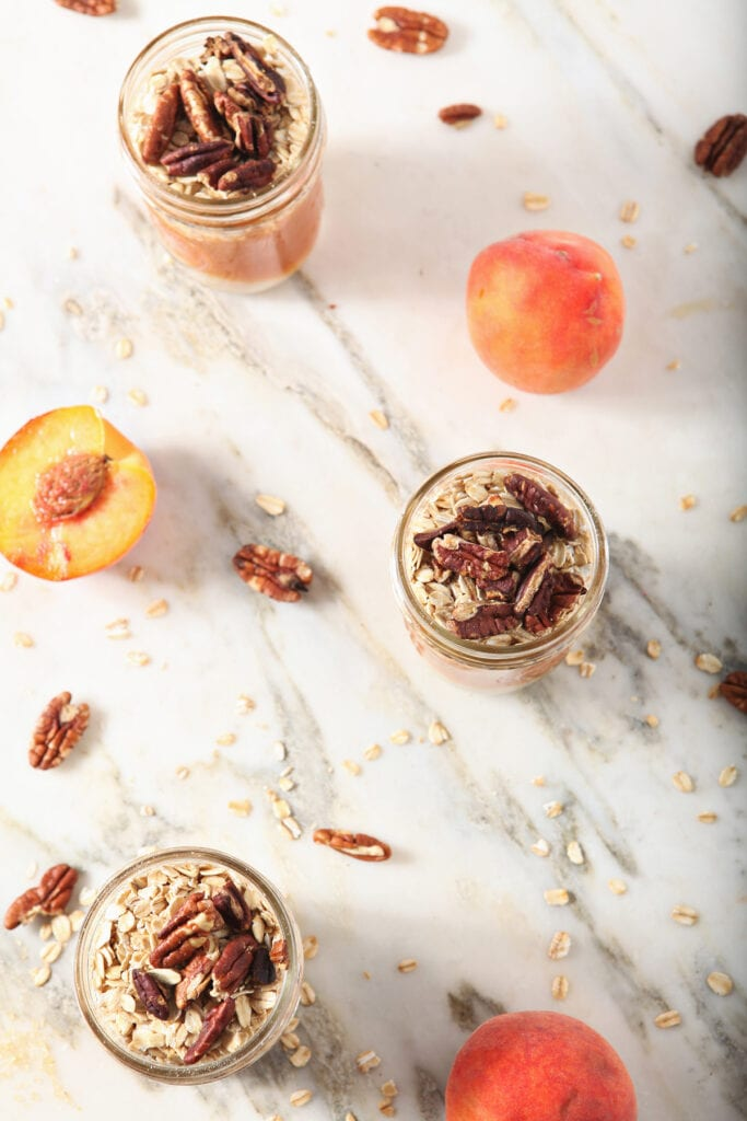 Three jars of Overnight Oats with pecans on marble