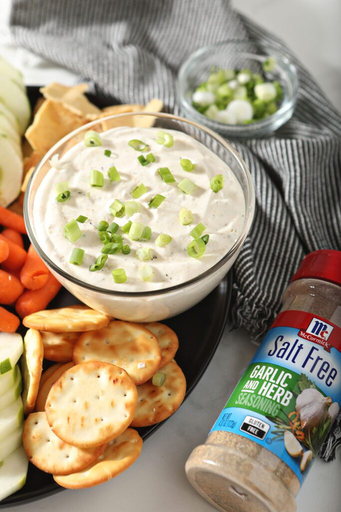 A bowl of Garlic and Herb Cream Cheese Dip with dippers and a jar of a McCormick spice blend