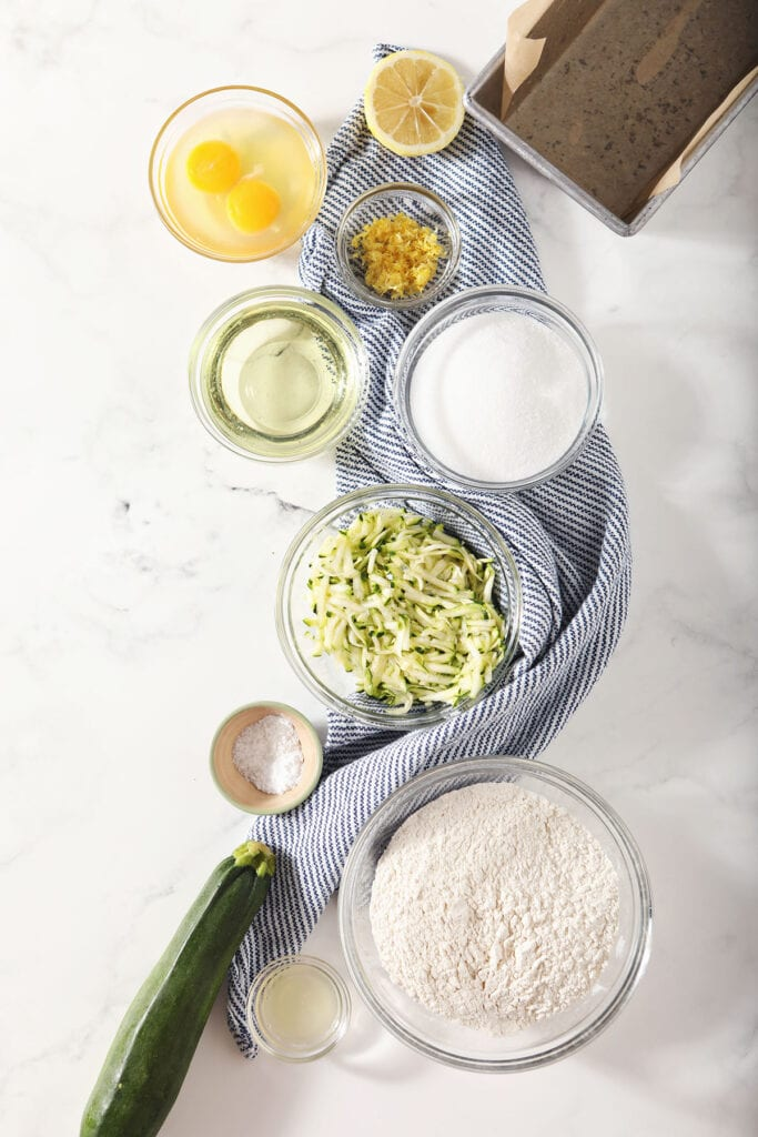 Ingredients for zucchini quick bread in bowls on marble