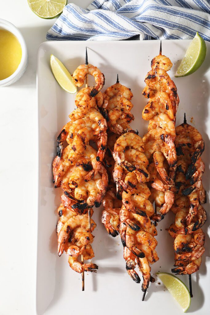 Skewered blackened shrimp with lime wedges on a white plate