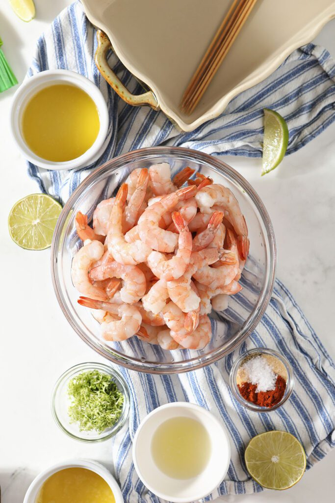 Raw shrimp in a bowl with seasonings in other bowls