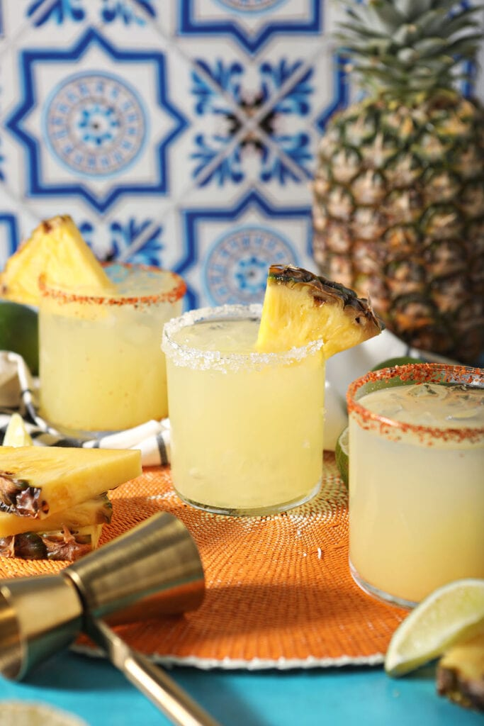 Three pineapple cocktails on an orange woven placemat