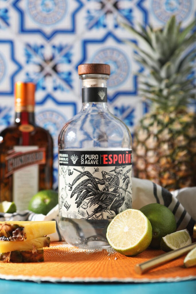 A bottle of tequila and other margarita ingredients