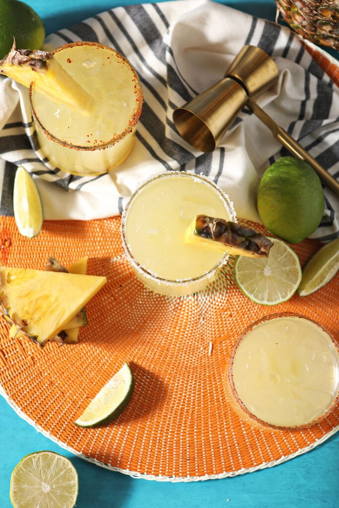 Three pineapple drinks with lime and pineapple wedges on an orange mat