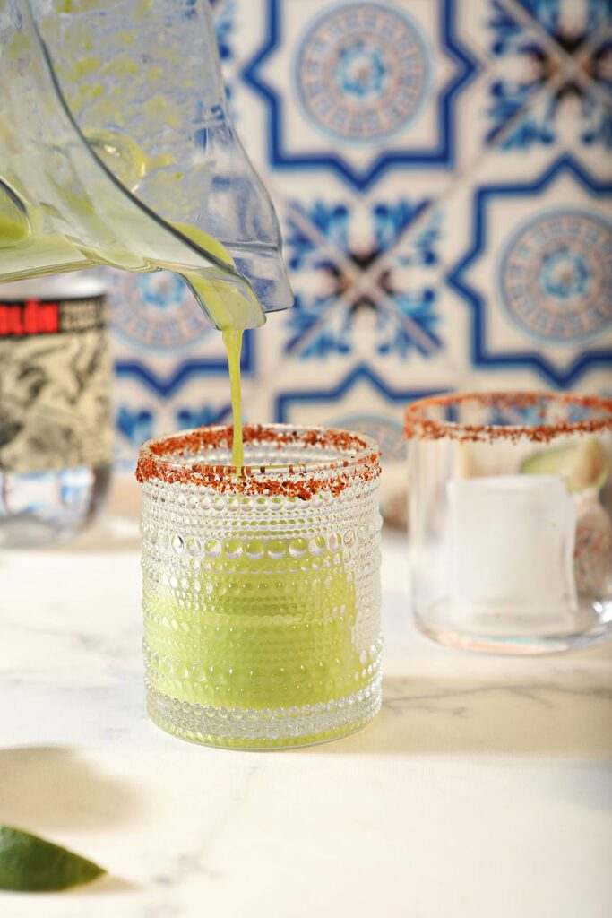 An avocado cocktail pours from a blender into a glass