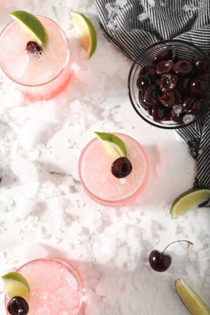 Three limeades with cherries and limes with ice and a bowl of cherries